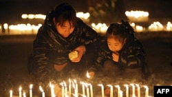 1 người đàn ông và 1 em bé thắp nến cầu nguyện cho 2 cha con gốc Hoa bị bắn chết, Rome, 10/1/2012