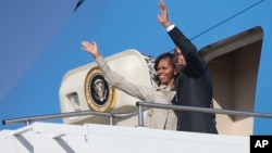 U.S. President Barack Obama and first lady Michelle Obama wave as they depart Waterkloof Air Base for a flight to Cape Town, June 30, 2013, in Centurion, South Africa.