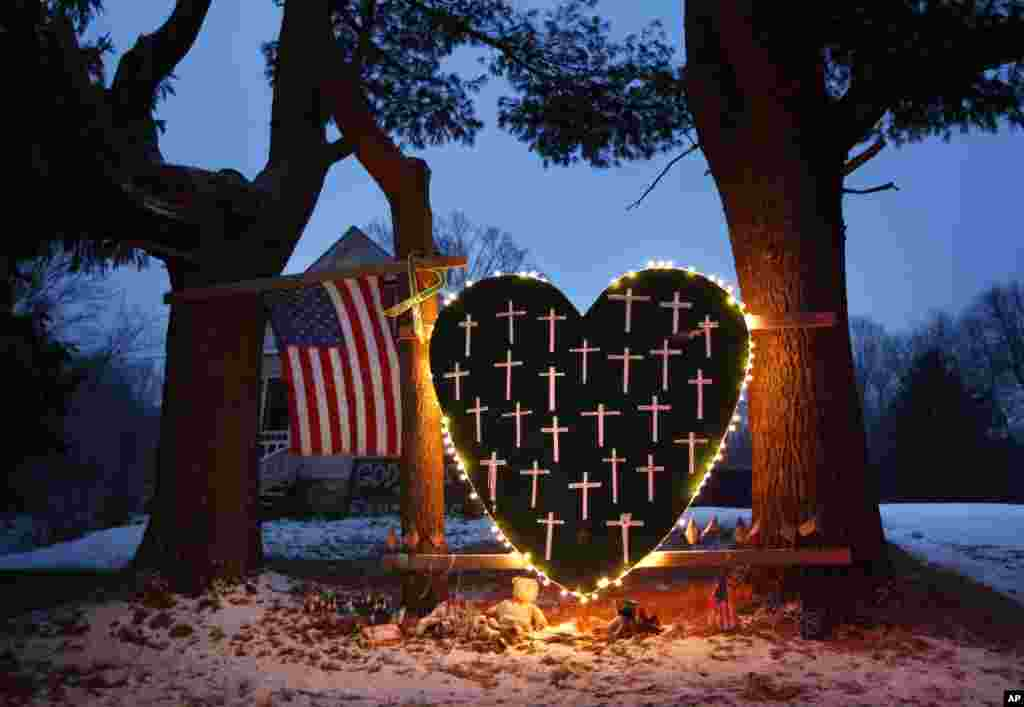A makeshift memorial with crosses for the victims of the Sandy Hook massacre stands outside a home in Newtown, Conn., Dec. 14, 2013.