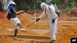 A man is sprayed with disinfectant after he celebrated the memory of a loved one who died due to the Ebola virus at a newly built grave yard for Ebola virus victims in Monrovia, Liberia, Wednesday, March 11, 2015. Liberians held a church service Wednesday for families who lost members to Ebola to mark the country's 99th celebration National Decoration Day, a holiday normally set aside for people to clean up and re-decorate the graves of their lost relatives. (AP Photo/Abbas Dulleh)