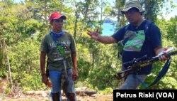 Rosek Nursahid (kanan) dari Profauna memberi penjelasan mengenai larangan berburu di hutan lindung Sendiki di Malang selatan kepada seorang warga (topi merah) yang kedapatan berburu di dalam hutan. (Foto: Petrus Riski/VOA).