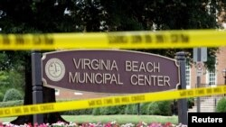 Police tape frames a sign at one of the entrances to the municipal government complex where a shooting incident occurred in Virginia Beach, Virginia, June 1, 2019.