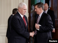 FILE - Vice President Mike Pence greets then-National Security Advisor Michael Flynn at the White House in Washington, Feb. 10, 2017.