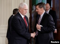 FILE - Vice President Mike Pence greets then-national security adviser Michael Flynn at the White House in Washington, Feb. 10, 2017.