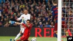 Cristiano Ronaldo marque le deuxième but du Real Madrid battant le gardien de Barcelone Claudio Bravo lors d'un match de football de La Liga espagnole surnommé «el clasico» opposant le Barcelone au Real Madrid, au stade Camp Nou à Barcelone, Espagne, 2 avril 2016.