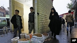 Pedestrians walk past vendor Amir Jamali, center, as he waits for customers after islamic leaders began cutting an estimated $100 billion a year in government subsidies for fuel and food, on a street in downtown Tehran, Iran, Nov 2010 (file photo)