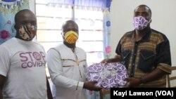 Remise des masques en tissu entre le SGA de BATIR, Fiacre Atsu (en blanc) et le directeur du collège Jean-Baptiste, Théophile Dika (en chemise imprimé wax), Lomé, le 4 juin 2020. (VOA/Kayi Lawson)