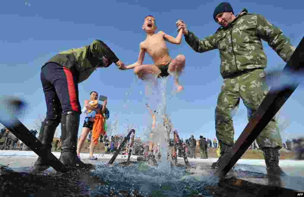 Dua tentara membantu seorang anak laki-laki mandi air es di sebuah danau di desa Leninskoe, pinggiran ibukota Bishkek, Kyrgyzstan.