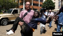FILE - A journalist rescues a woman injured in a shootout between armed men and police at Nairobi's Westgate shopping mall, Sept. 21, 2013. A new report shows journalists' vulnerability to PTSD after covering extreme violence.