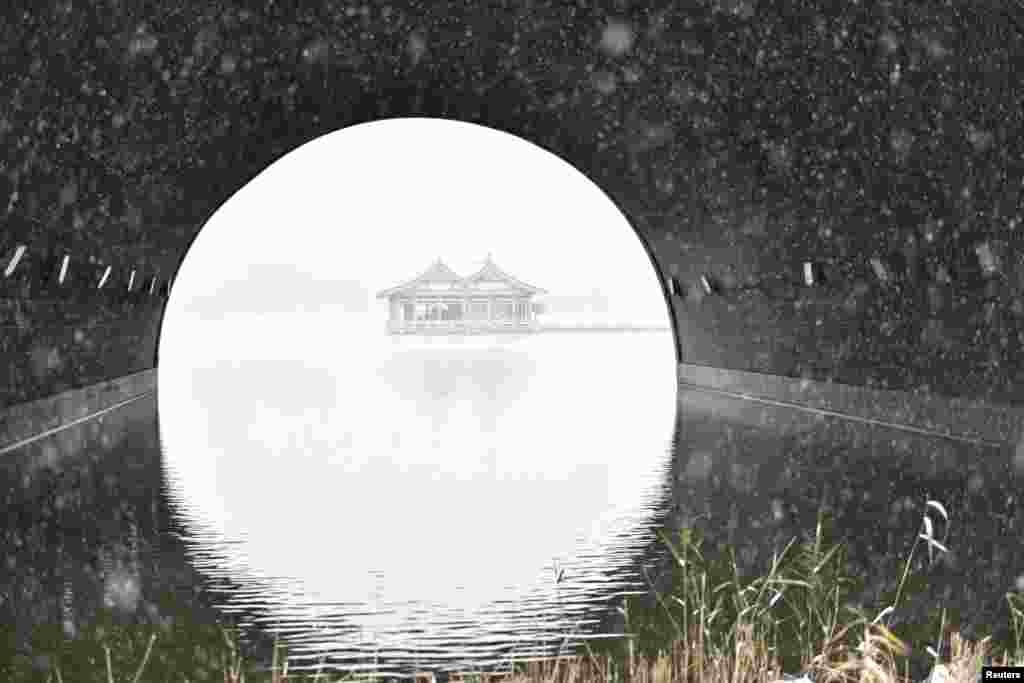 ផ្ទះបុរាណមួយខ្នងនៅលើបឹងមួយនៅថ្ងៃធ្លាក់ព្រិលក្នុងក្រុង Xi'an ខេត្ត Shaanxi ប្រទេសចិន កាលពីថ្ងៃទី២២ ខែវិច្ឆិកា ឆ្នាំ២០១៦។
