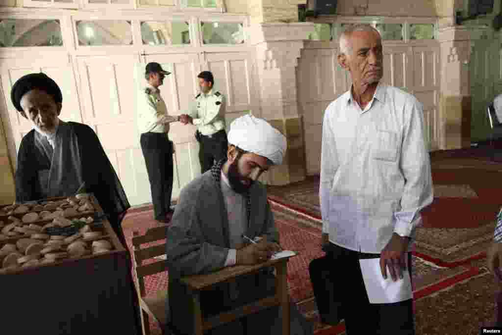 14일 이란 콤의 모스크 투표소에서 투표 용지를 작성하는 성직자들.