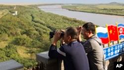 在中国吉林省延边地区,在中朝边界附近的一个观察站,一名男子用望远镜张望。(2017年9月9日)