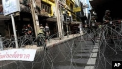 Thai soldiers and riot policemen stand beside barbed wire after they sealed off part of a tourist district on Sukhumvit road in downtown Bangkok, in May.