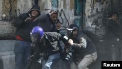 1月25日在开罗的解放广场,抗议者与警察发生冲突,这是抗议者和摄影记者躲避警方攻击的一个画面