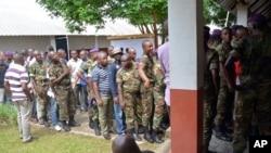 Des soldats et des civils congolais font la queue pour voter devant un bureau de vote, à Brazzaville, République du Congo, 20 mars 2016. (AP Photo/John Bompengo)