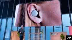Rick Osterloh, Senior Vice President of Devices and Services at Google, speaks about Pixel Buds (displayed on screen) as this and other products were announced Tuesday, Oct. 15, 2019, in New York. (AP Photo/Craig Ruttle)