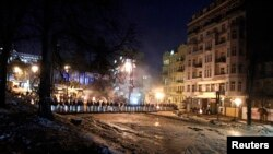 Riot police stand in a cordon facing a barricade of anti-government protesters in Kyiv, Feb. 3, 2014.
