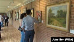Visitors study some of the works on display in the refugee exhibit at the Sandy Spring Museum in Maryland. Many of the works depict scenes from the artists' home countries.