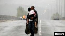 یک پناهجوی اهل سوریه در حال بوسیدن فرزند خود و راه رفتن در زیر باران به سمت مرز مشترک مقدونیه با یونان
