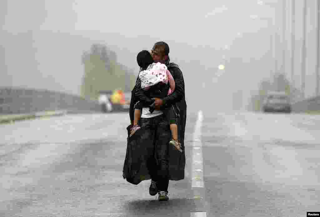 A Syrian refugee kisses his son as he walks through a rainstorm toward Greece's border with Macedonia, near the Greek village of Idomeni.