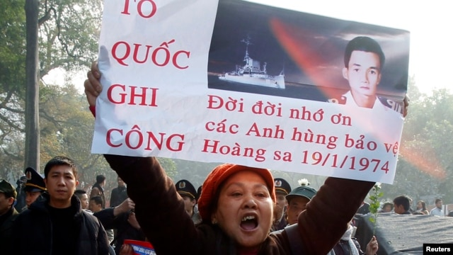 Một người chống Trung quốc tham gia cuộc biểu tình ở Hà Nội, cầm bức ảnh thuyền trưởng Ngụy Văn Thà, người hy sinh trong trận Hải chiến Hoàng Sa, vào ngày kỷ niệm 40 năm trận Hải chiến 19/1/2014