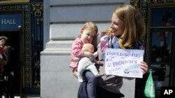 Kim Tarner nosi ćerku Adelajd na skupu podrške inicijativi o plaćenom odusustvu za roditelje novorodjene dece.