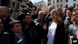 Giorgia Meloni makes the victory sign as he meets reporters in Rome's Pantheon Square, March 16, 2016.