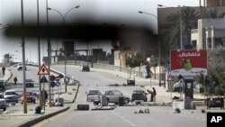 An impromptu roadblock is seen through a car windscreen in Tripoli, Libya, February 26, 2011