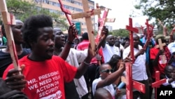People hold wooden crosses to represent those killed in a string of attacks, during a demonstration to demand greater security, in Nairobi, Kenya, Nov. 25, 2014.