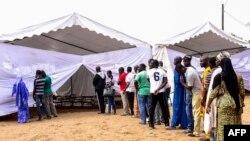 Voters line up prior to casting their vote in Senegal's legislative election, July 30, 2017, in Dakar.