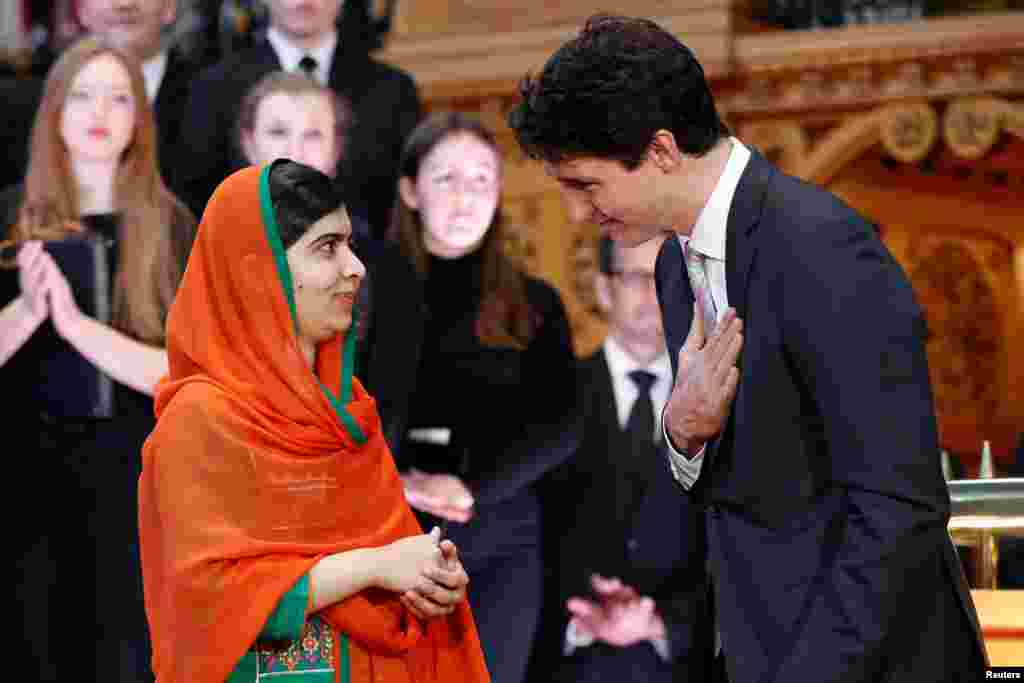 Canada's Prime Minister Justin Trudeau (R) gestures toward Pakistani Nobel Peace Prize laureate Malala Yousafzai after presenting her with honorary Canadian citizenship during a ceremony in the Library of Parliament on Parliament Hill in Ottawa, Ontario.