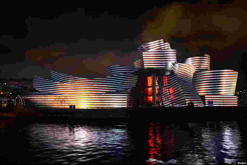"""Museum Guggenheim disinari cahaya warna-warni pada acara pertunjukan cahaya berjudul """"Reflections"""" (Pantulan) di kota Bilbao, Spanyol."""