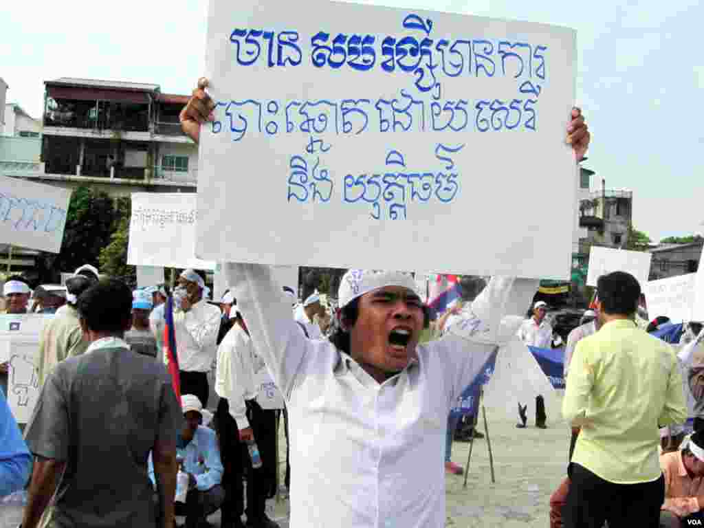 "A protester holds a sign that reads ""With Sam Rainsy [presence], there will be free and fair elections."" (Khoun Theara/VOA Khmer)"