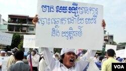 """Một người biểu tình cầm biểu ngữ với dòng chữ """"Có Sam Rainsy sẽ có bầu cử tự do và công bằng"""""""