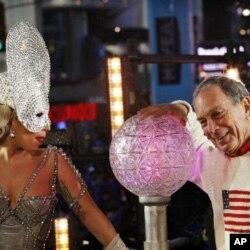 ນັກຮ້ອງຊື່ດັງ Lady Gaga ແລະເຈົ້າຄອງກໍາແພງນະຄອນນິວຢອກ ທ່ານ Michael Bloomberg ຖ່າຍຮູບຮ່ວມກັນກ່ອນຈະກົດປຸ່ມໃຫ້ ໜ່ວຍແກ້ວຄ່ອຍໆໄຫລລົງ ຂະນະນັບຖອຍຫລັງໄປຫາປີໃໝ່ ທີ່ຈະຕຸ ລັດ Times Square, ກ່ອນທ່ຽງຄືນວັນທີ 31 ທັນວາ 2011. REUTERS/Eduardo Munoz