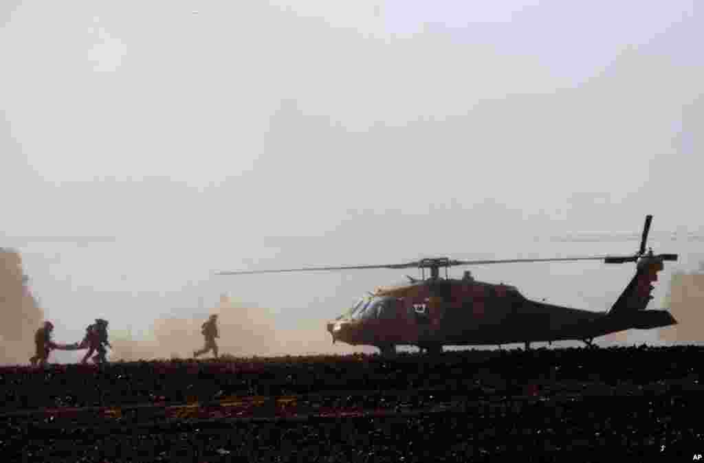 Israeli soldiers carry a wounded soldier to a helicopter near the Israel and Gaza border, July 24, 2014.