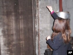 Rebecca Maitland points out the chute where merchants used to drop their gold from the street above.