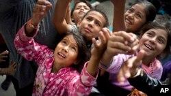 Niños migrantes, que forman parte de las caravanas de centroamericanos que buscan asilo en EE.UU., esperando caramelos que les ofreció un trabajador social en el refugio en Tijuana, el martes 20 de noviembre de 2018.