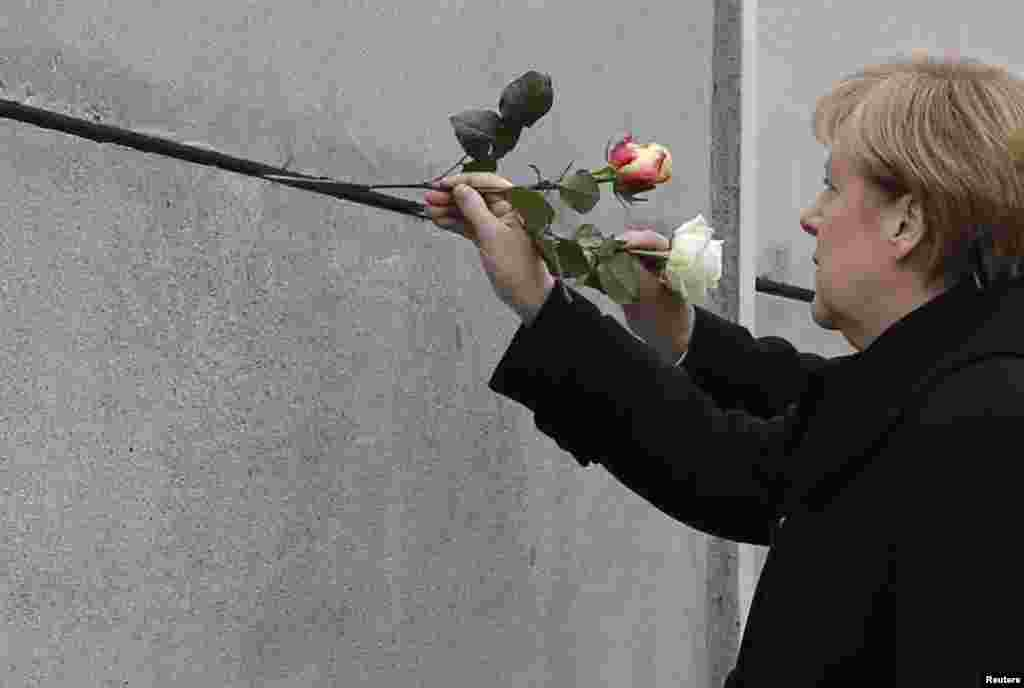 German Chancellor Angela Merkel places a rose at the Berlin Wall memorial in Bernauer Strasse, during a ceremony marking the 25th anniversary of the fall of the Berlin Wall, Berlin, Germany.