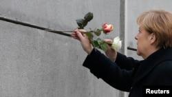 La canciller alemana, Angela Merkel, coloca una rosa en el Muro de Berlín sobre la Bernauer Strasse, como parte de los actos para conmemorar el 25 aniversario de la caída del muro que dividió la capital alemana.