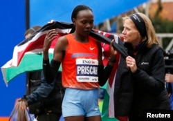Priscah Jeptoo (L) of Kenya is wrapped in the Kenyan flag by Mary Wittenberg, president of the New York Road Runners, after Jeptoo crossed the finish line to win the women's division of the New York City Marathon, Nov. 3, 2013.