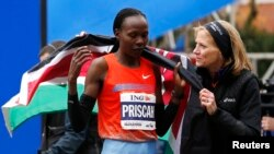 Priscah Jeptoo (kiri) dari Kenya setelah melintasi garis finish dan memenangkan Maraton New York kategori wanita (3/11). (Reuters/Mike Segar)