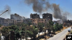 In this Sunday, July 7, 2013, citizen journalism image, which has been authenticated based on its contents and other AP reporting, black smoke rises from buildings damaged by Syrian government airstrikes and shelling in Homs.