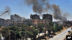 In this July 7, 2013, citizen journalism image provided by Lens Young Homsi, black smoke rises from buildings damaged by Syrian government airstrikes and shelling in Homs, Syria.