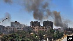Asap hitam tampak mengepul setelah serangan pasukan Suriah di kota Homs (7/7).