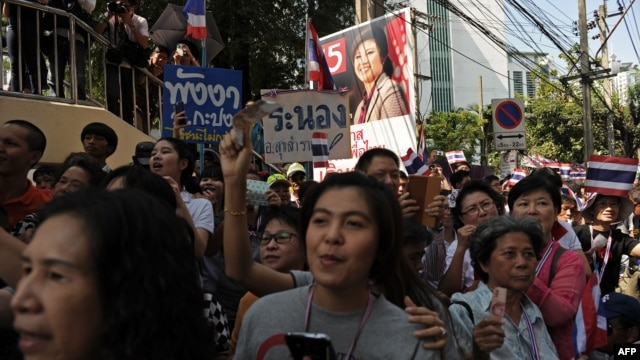 Thai supporters stand beside an electoral campaign poster of prime minister Yingluck Shinawatra (top) as they cheer on anti-government protesters marching along the streets in downtown Bangkok, Jan. 30, 2014.