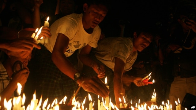 Protesters hold candles during a candlelight vigil at Sule Pagoda in Rangoon, Burma, May 23, 2012.