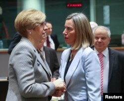 Italy's Defense Minister Roberta Pinotti (L) talks with European Union foreign policy chief Federica Mogherini during a European Union foreign and defense ministers meeting in Brussels, March 6, 2018.