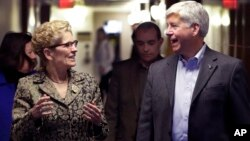 FILE - Michigan Gov. Rick Snyder and Ontario Premier Kathleen Wynne walk to a news conference, March 13, 2017, in Detroit. Snyder and Wynne stressed that they want their voices heard as President Donald Trump demands a negotiation of trade policies betwee