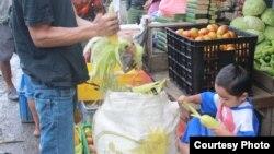 Seorang pedagang di pasar Cisarua, Bogor, mengupas kulit jagung dibantu anaknya yang masih kecil.